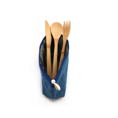Bamboo cutlery poking up out of blue hemp bag view from the front with white background