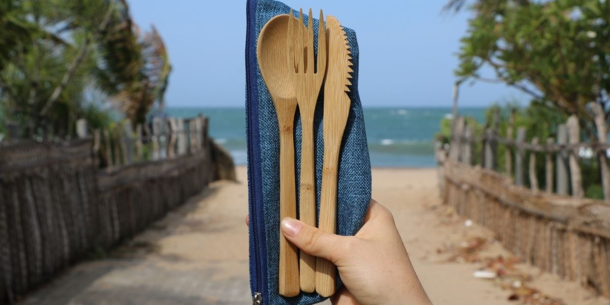 Cutlery and bag held by hand in front of beach