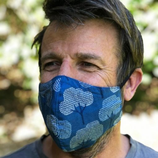 Man wearing blue face mask with white trees