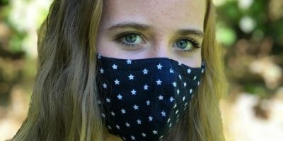 A girl stares at the camera in navy mask with white stars.
