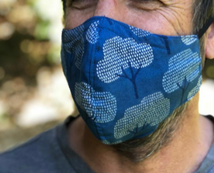 Extra close up of Man wearing cotton blue tree mask. Click for more information about the mask
