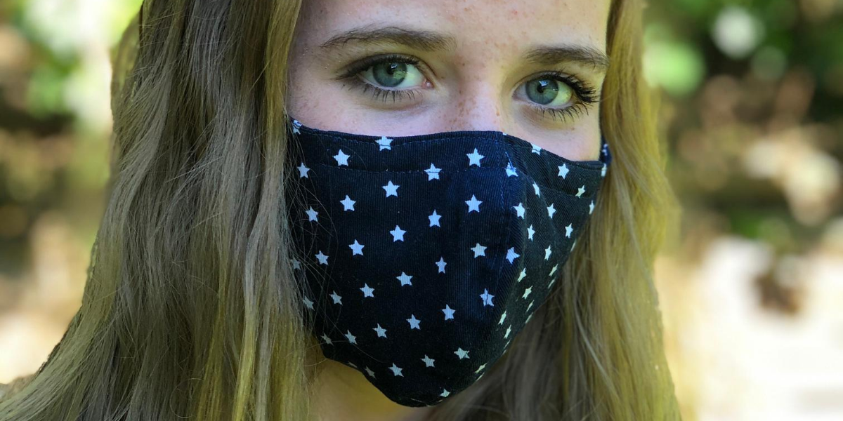 Close up head shot of teenager wearing navy blue mask with white stars
