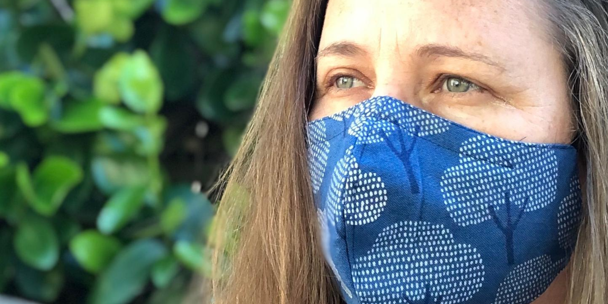 Woman looks to the left wearing blue fabric face mask