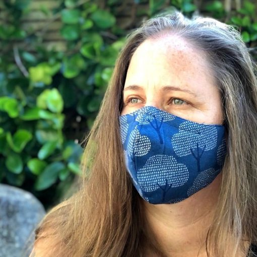 Head shot of woman wearing blue tree mask out in nature